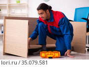 Young male contractor repairing furniture in the office. Стоковое фото, фотограф Elnur / Фотобанк Лори