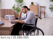 Young disabled employee suffering at workplace. Стоковое фото, фотограф Elnur / Фотобанк Лори