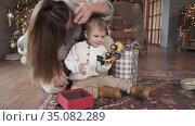 Mom and son sort gifts. Редакционное видео, видеограф Потийко Сергей / Фотобанк Лори