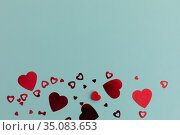 High angle view of red metallic hearts on blue background. Стоковое фото, агентство Wavebreak Media / Фотобанк Лори