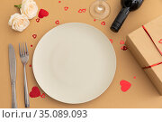 White plate, hearts, roses and wine on brown background. Стоковое фото, агентство Wavebreak Media / Фотобанк Лори