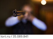 Muzzle of single barrelled shotgun on blurred background of aiming man. Стоковое фото, фотограф Яков Филимонов / Фотобанк Лори