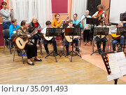 Classical music concert for parents is in Russian children music school. Boys and girls with adults play quitar together (2020 год). Редакционное фото, фотограф Кекяляйнен Андрей / Фотобанк Лори