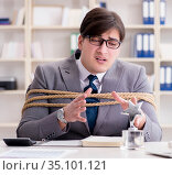Businessman tied up with rope in office. Стоковое фото, фотограф Elnur / Фотобанк Лори