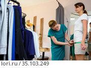 Девушка портной измеряет размер бедер заказчика. Стоковое фото, фотограф Иванов Алексей / Фотобанк Лори