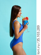 Woman in swimsuit poses with coctail, side view. Стоковое фото, фотограф Tryapitsyn Sergiy / Фотобанк Лори