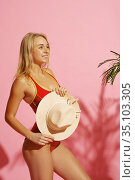 Young woman in swimsuit holds hat in studio. Стоковое фото, фотограф Tryapitsyn Sergiy / Фотобанк Лори