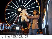 Happy woman hugs soft toy in night amusement park. Стоковое фото, фотограф Tryapitsyn Sergiy / Фотобанк Лори