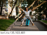 Playful woman riding on suitcase in summer park. Стоковое фото, фотограф Tryapitsyn Sergiy / Фотобанк Лори