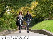 Trendy fashinable teenagers riding public rental electric scooters in urban city park. New eco-friendly modern public city transport in Ljubljana, Slovenia. Стоковое фото, фотограф Matej Kastelic / Фотобанк Лори