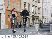 Trendy fashinable teenagers riding public rental electric scooters in urban city environment. New eco-friendly modern public city transport in Ljubljana, Slovenia. Стоковое фото, фотограф Matej Kastelic / Фотобанк Лори
