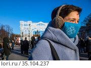 Люди носят защитные маски во время резкого похолодания в городе Москве на фоне новогодних инсталляций на Пушкинской площади в центре города, Россия. Редакционное фото, фотограф Николай Винокуров / Фотобанк Лори