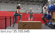 Diverse man and woman jumping on box wearing face masks at gym, caucasian woman timing. Стоковое видео, агентство Wavebreak Media / Фотобанк Лори