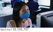 Asian woman wearing face mask using computer while sitting on her desk at modern office. Стоковое видео, агентство Wavebreak Media / Фотобанк Лори