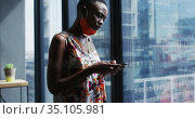 African american woman with face mask around her neck using smartphone at modern office. Стоковое видео, агентство Wavebreak Media / Фотобанк Лори
