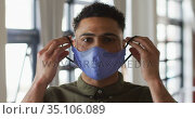 Portrait of mixed race man putting mask on. Стоковое видео, агентство Wavebreak Media / Фотобанк Лори