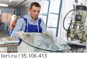 Male glazier with female assistant working on curved glass beveling machine. Стоковое фото, фотограф Яков Филимонов / Фотобанк Лори