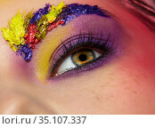 Close-up photo of female eye with unusual art make-up and face painting on brows and around eye. Стоковое фото, фотограф Serg Zastavkin / Фотобанк Лори