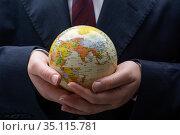 Businessman is standing with an earth globe fot business concept. Стоковое фото, фотограф Turgay Koca / easy Fotostock / Фотобанк Лори