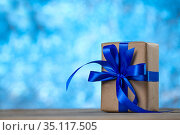 Gift box with a ribbon bow on the desk on blue abstract background. Стоковое фото, фотограф Иван Карпов / Фотобанк Лори