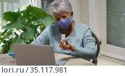 Senior mixed race woman wearing face mask having medical consultation using laptop. Стоковое видео, агентство Wavebreak Media / Фотобанк Лори