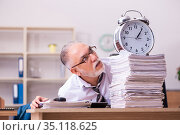 Old male employee unhappy with excessive work in the office. Стоковое фото, фотограф Elnur / Фотобанк Лори