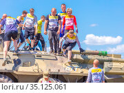 Russia, Samara, June 2019: young athletic people, participants in the hero race, climb through an armored personnel carrier in the village of Roshchinsky near Samara. Text in Russian: race of heroes, platoon. Редакционное фото, фотограф Акиньшин Владимир / Фотобанк Лори