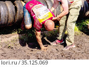 Russia, Samara, June 2019: athletic youth participates in a race of heroes and overcomes obstacles car tires on a summer day in the village of Roshchinsky . Text in Russian: race of heroes, platoon. Редакционное фото, фотограф Акиньшин Владимир / Фотобанк Лори