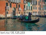 Гондола перевозит людей через Гранд канал солнечным утром. Венеция, Италия (2017 год). Редакционное фото, фотограф Виктор Карасев / Фотобанк Лори