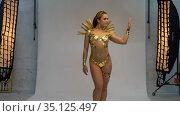 Sexy woman with golden tapes on body walk on white background backstage. Стоковое видео, видеограф Гурьянов Андрей / Фотобанк Лори