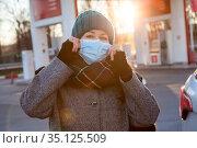 Adult female driver wearing face mask when going to refuel her car on petrol station. Стоковое фото, фотограф Кекяляйнен Андрей / Фотобанк Лори