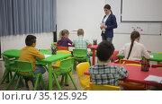 Young female teacher standing at whiteboard in classroom, conducting lesson with children. Стоковое видео, видеограф Яков Филимонов / Фотобанк Лори