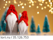 Two Christmas gnomes in red hats on a gold background. Стоковое фото, фотограф Евдокимов Максим / Фотобанк Лори