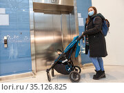 Mother wearing face mask waiting elevator with children pram in hall of shopping mall. Стоковое фото, фотограф Кекяляйнен Андрей / Фотобанк Лори