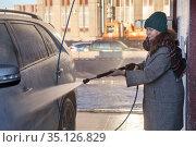 Attractive woman washing her car in a self-service carwash station at winter season. Стоковое фото, фотограф Кекяляйнен Андрей / Фотобанк Лори