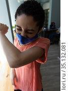Mixed race woman wearing face mask sneezing into her elbow. Стоковое фото, агентство Wavebreak Media / Фотобанк Лори