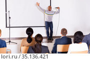 Excited Hispanic preacher giving motivational speech from stage. Стоковое фото, фотограф Яков Филимонов / Фотобанк Лори