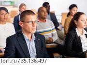 Focused businessman listening to speaker at business conference. Стоковое фото, фотограф Яков Филимонов / Фотобанк Лори