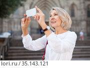 Mature woman is taking photos on her camera while journey through the city. Стоковое фото, фотограф Яков Филимонов / Фотобанк Лори