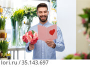 happy man with valentine's day card at flower shop. Стоковое фото, фотограф Syda Productions / Фотобанк Лори