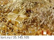 Новогодний подарок в золотой коробке. Оформлен блестящей мишурой. Стоковое фото, фотограф ирина реброва / Фотобанк Лори