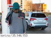 Female driver paying for diesel via credit card machine, self service petrol station without staff, rear view. Стоковое фото, фотограф Кекяляйнен Андрей / Фотобанк Лори