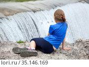 Rear view at preteen age girl sitting on edge of waterfall of the Cijevna river. It is called Montenegrin Niagara Falls. Surroundings of Podgorica city. Montenegro, Europe. Стоковое фото, фотограф Кекяляйнен Андрей / Фотобанк Лори