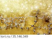 Сверкающая новогодняя открытка. Подарок в золотой коробке. Оформлен блестящей мишурой. Стоковое фото, фотограф ирина реброва / Фотобанк Лори