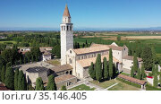 View from drone of medieval Basilica di Santa Maria Assunta, principal church in small Italian town of Aquileia on sunny autumn day. Стоковое видео, видеограф Яков Филимонов / Фотобанк Лори