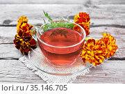 Чай травяной из бархатцев в чашке на доске. Стоковое фото, фотограф Резеда Костылева / Фотобанк Лори