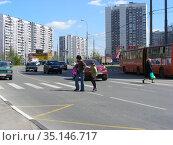 Люди переходят дорогу по пешеходному переходу. Новокосинская улица. Район Новокосино. Город Москва (2012 год). Редакционное фото, фотограф lana1501 / Фотобанк Лори