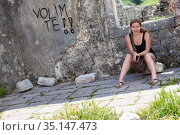 Frustrated teen age girl sitting in ruined place with inscription on wall I love you in Croatian. Стоковое фото, фотограф Кекяляйнен Андрей / Фотобанк Лори