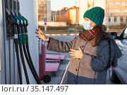 A woman with protective mask chooses a brand of fuel at a gas station for a car. Warm clothes, winter season. Стоковое фото, фотограф Кекяляйнен Андрей / Фотобанк Лори