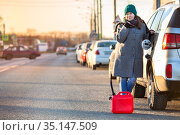 Attractive woman with empty gas tank standing on roadside with red plastic canister, copy space. Стоковое фото, фотограф Кекяляйнен Андрей / Фотобанк Лори